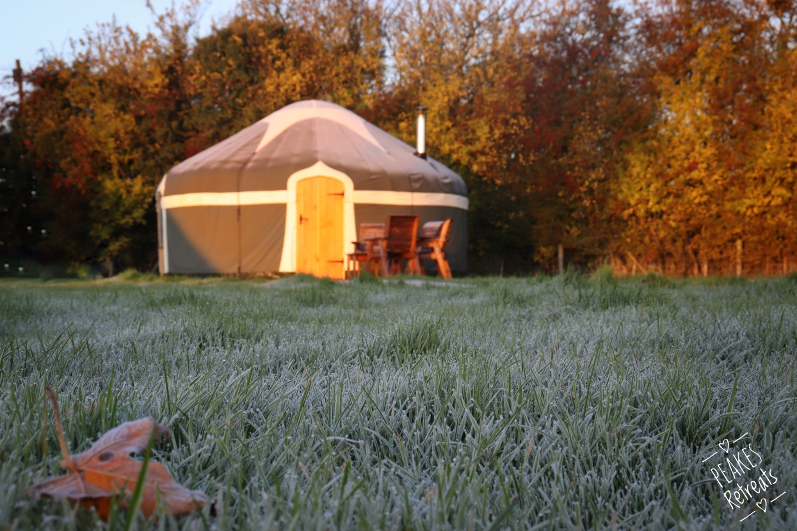 Autumnal frost on field with yurt