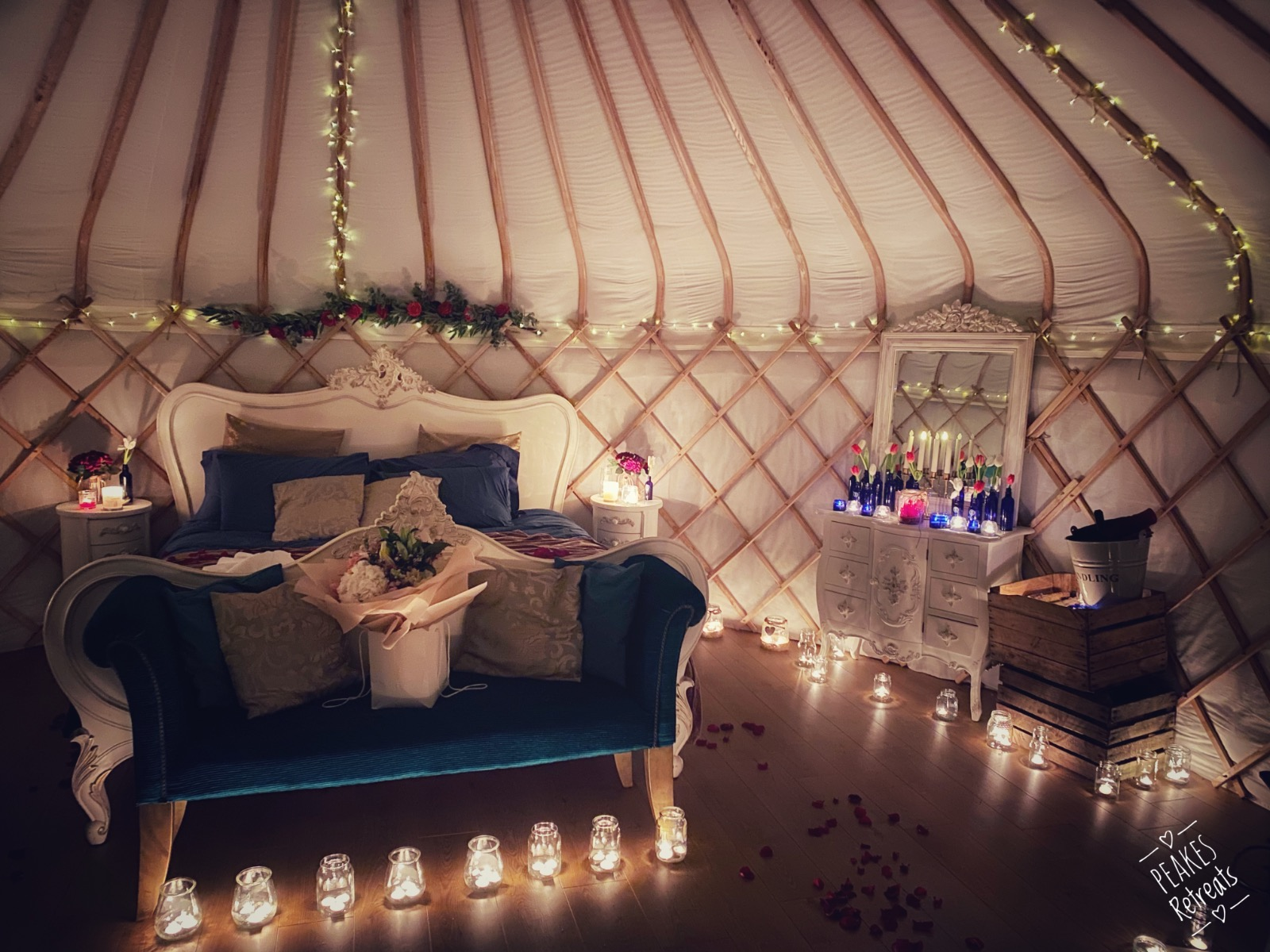 Romantic glamping yurt interior, superkingsize bed, candles and flowers