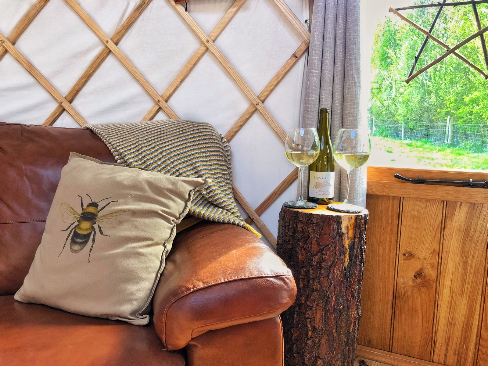 Brown leather sofa, bottle of Sancerre on log table in glamping yurt