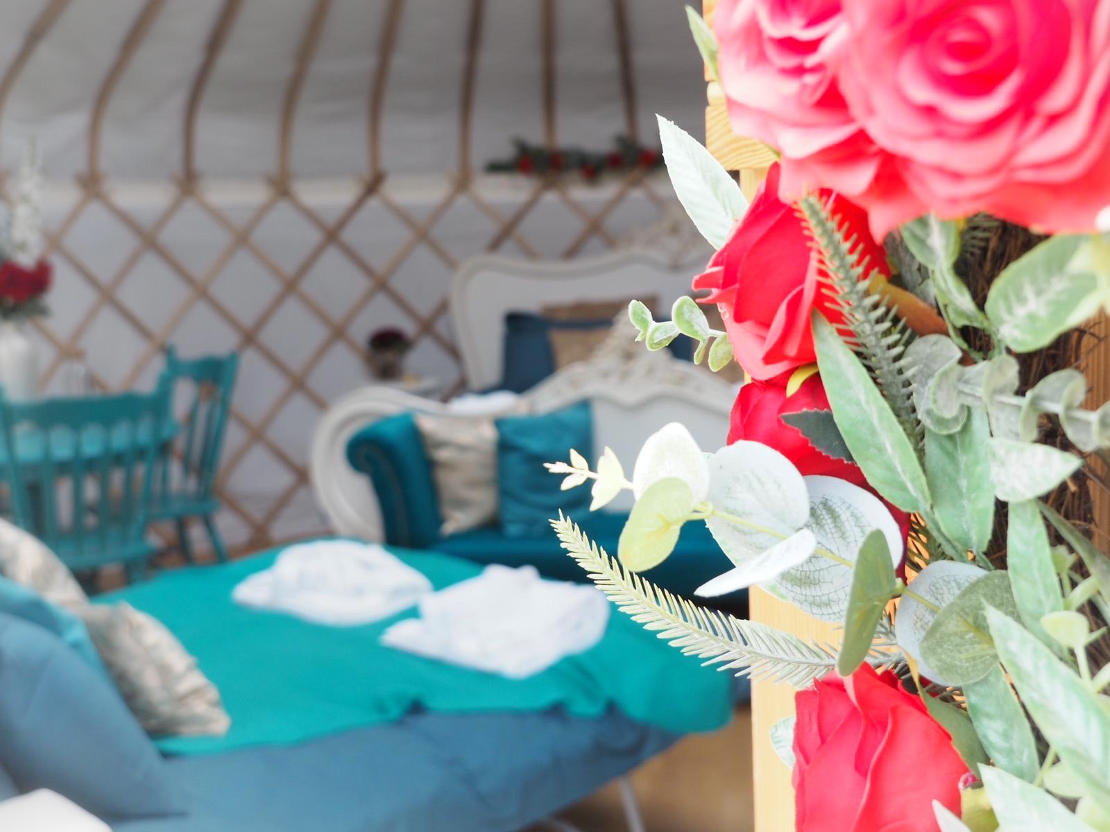 Red rose faux flower wreath, teal glamping yurt interior