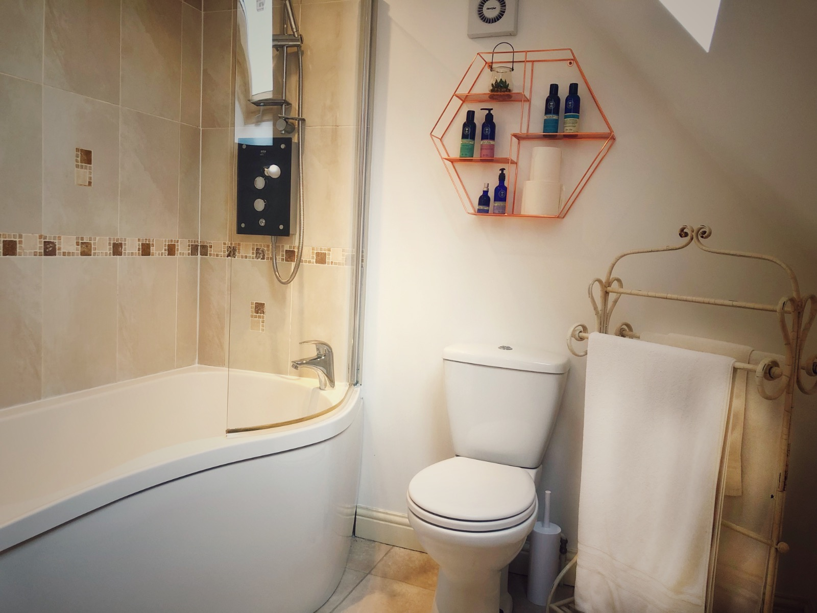 Bath with shower, Rosegold shelves, Neals Yard toiletries, beautiful bathroom