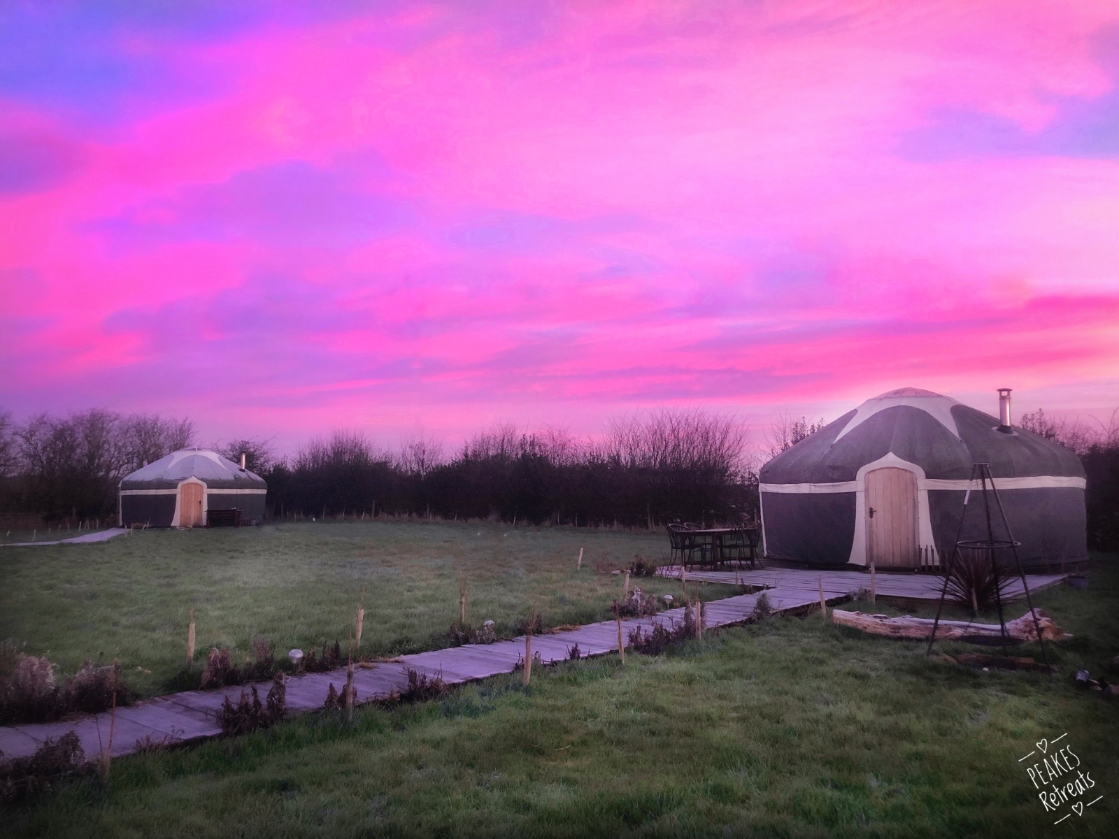 Pink sunrise over English countryside glamping yurts