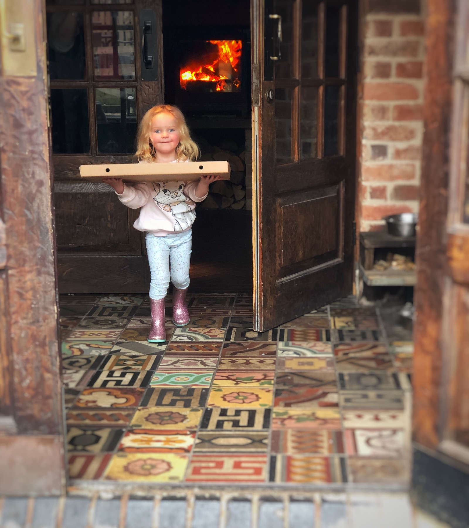 Little girl carrying large pizza, roaring fire