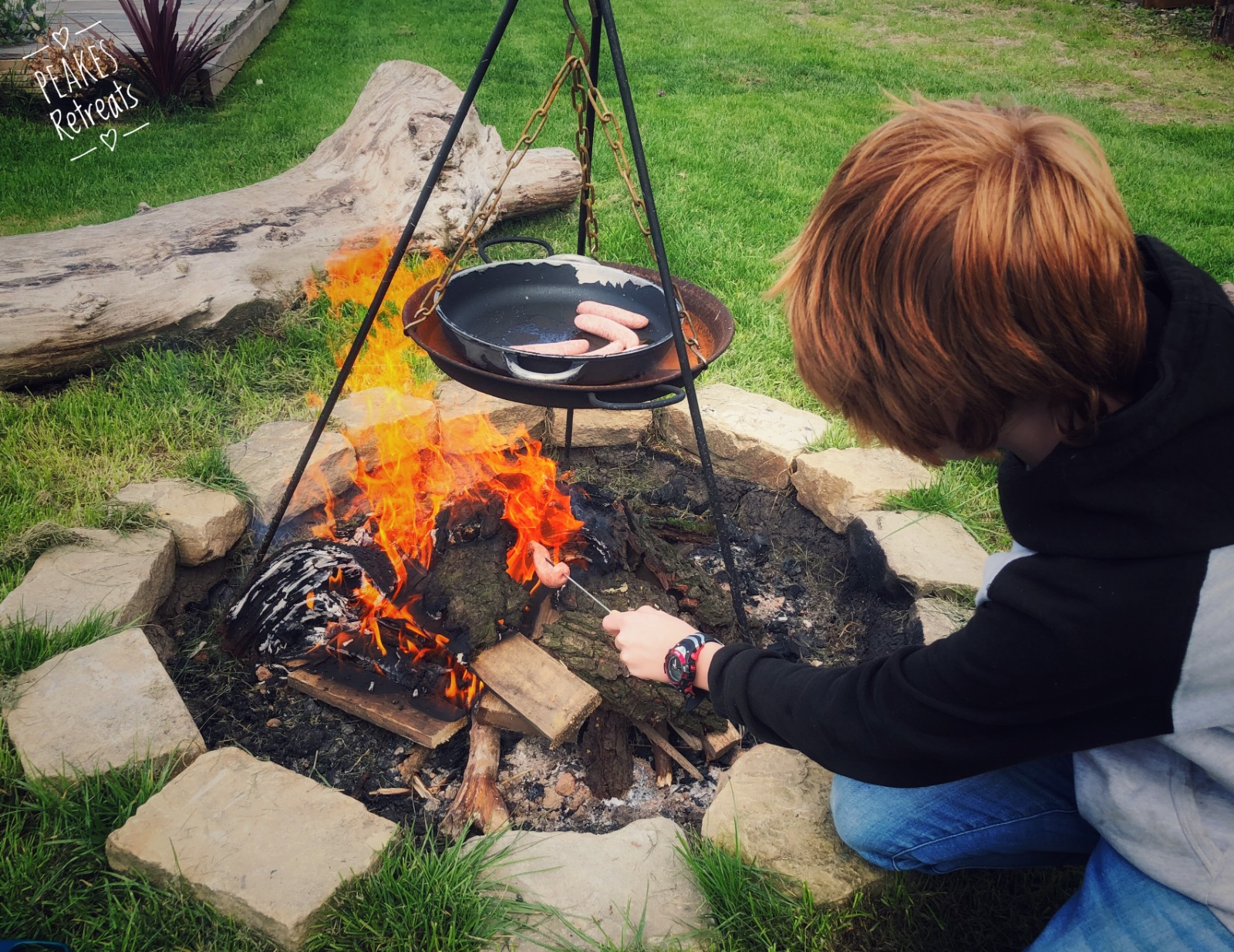 Boy toasting marshmallows over a campfire