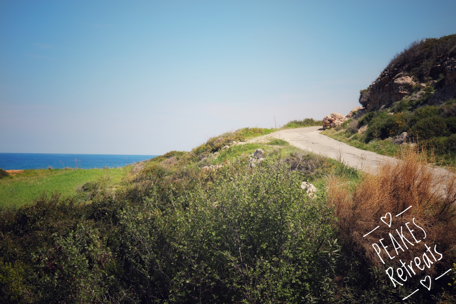 Winding narrow road next to the blue sea