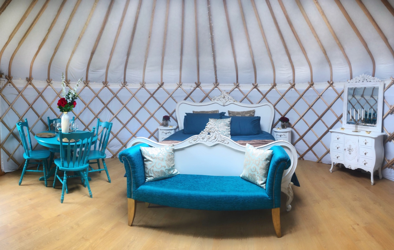 Beautiful Teal bedding with red roses in lovely glamping yurt