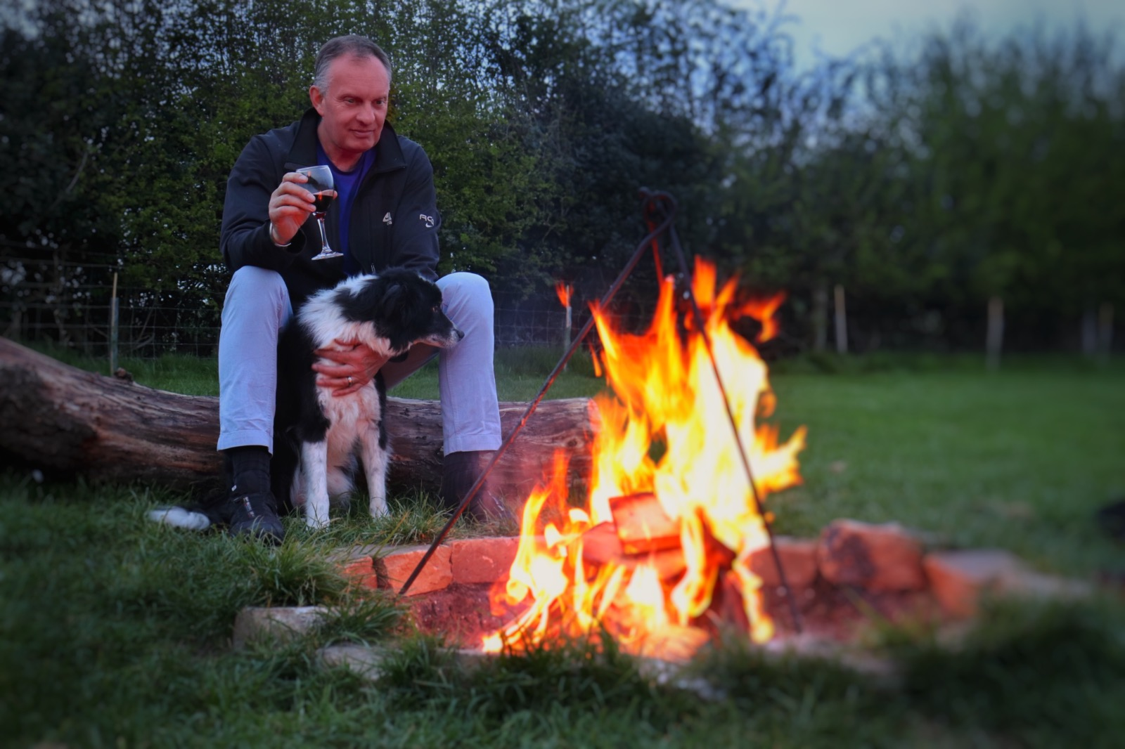 Man and dog by firepit on camping holiday