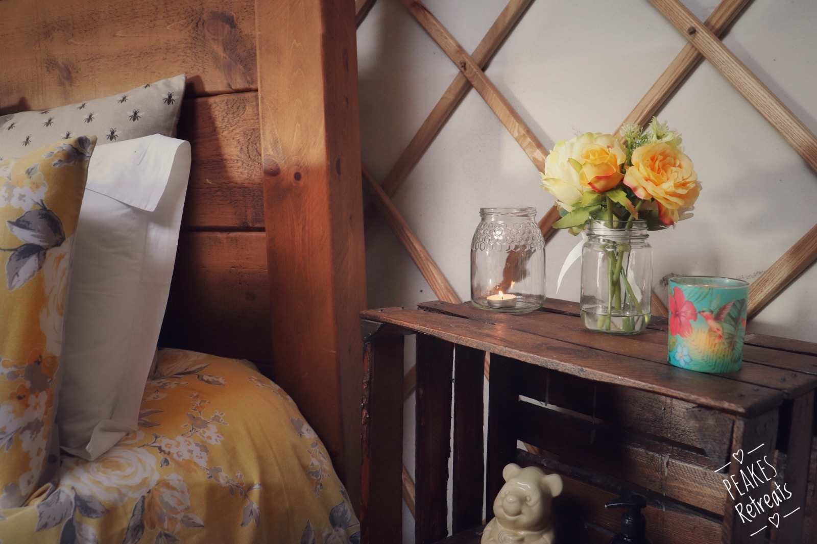 Upcycled apple crate bedside tables, with candles next to rustic wooden four poster bed