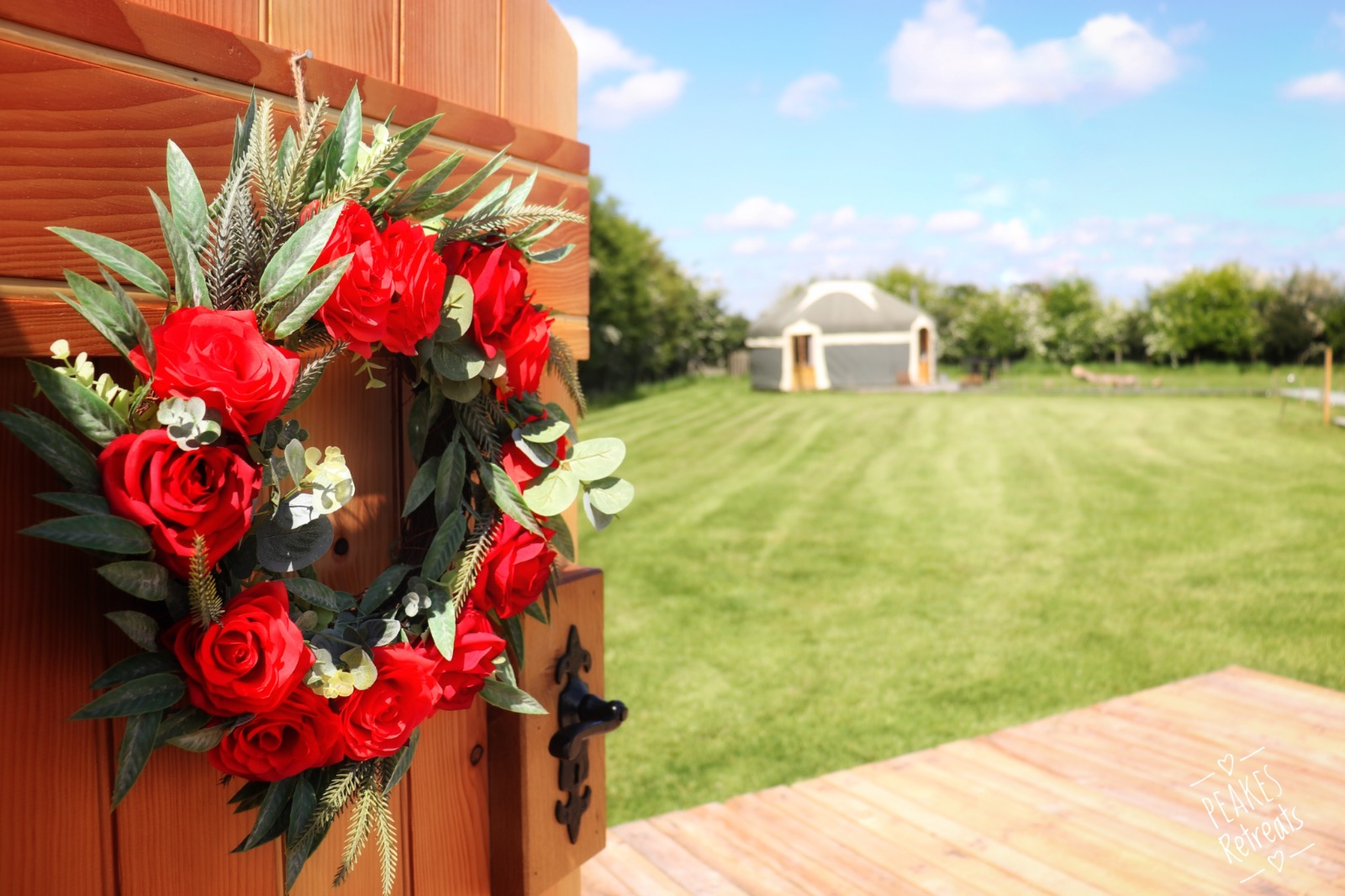 Red rose wreath, on yurt door, with views over glamping field