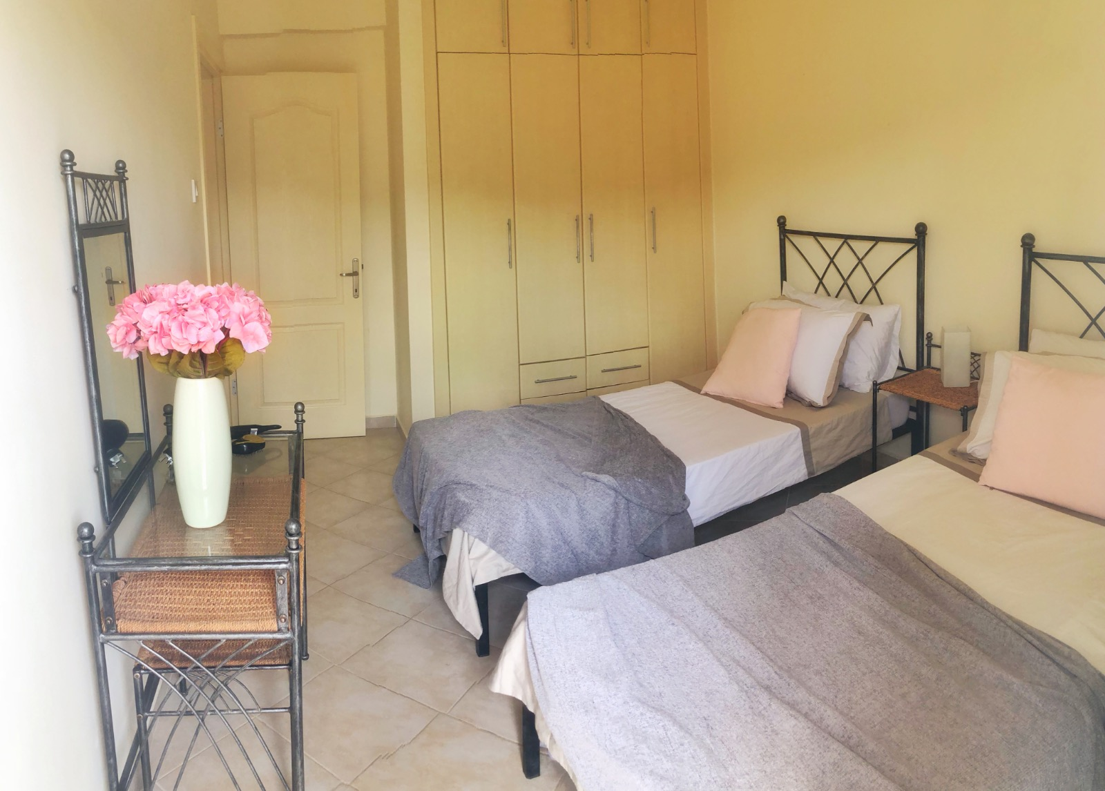 Twin bedroom in apartment with large fitted wardrobes,
