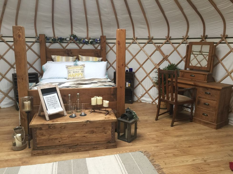 Rustic king size chunky wooden bed, and matching dressing table from Indigo Furniture makes a fantastic yurt interior for a luxury glamping experience.