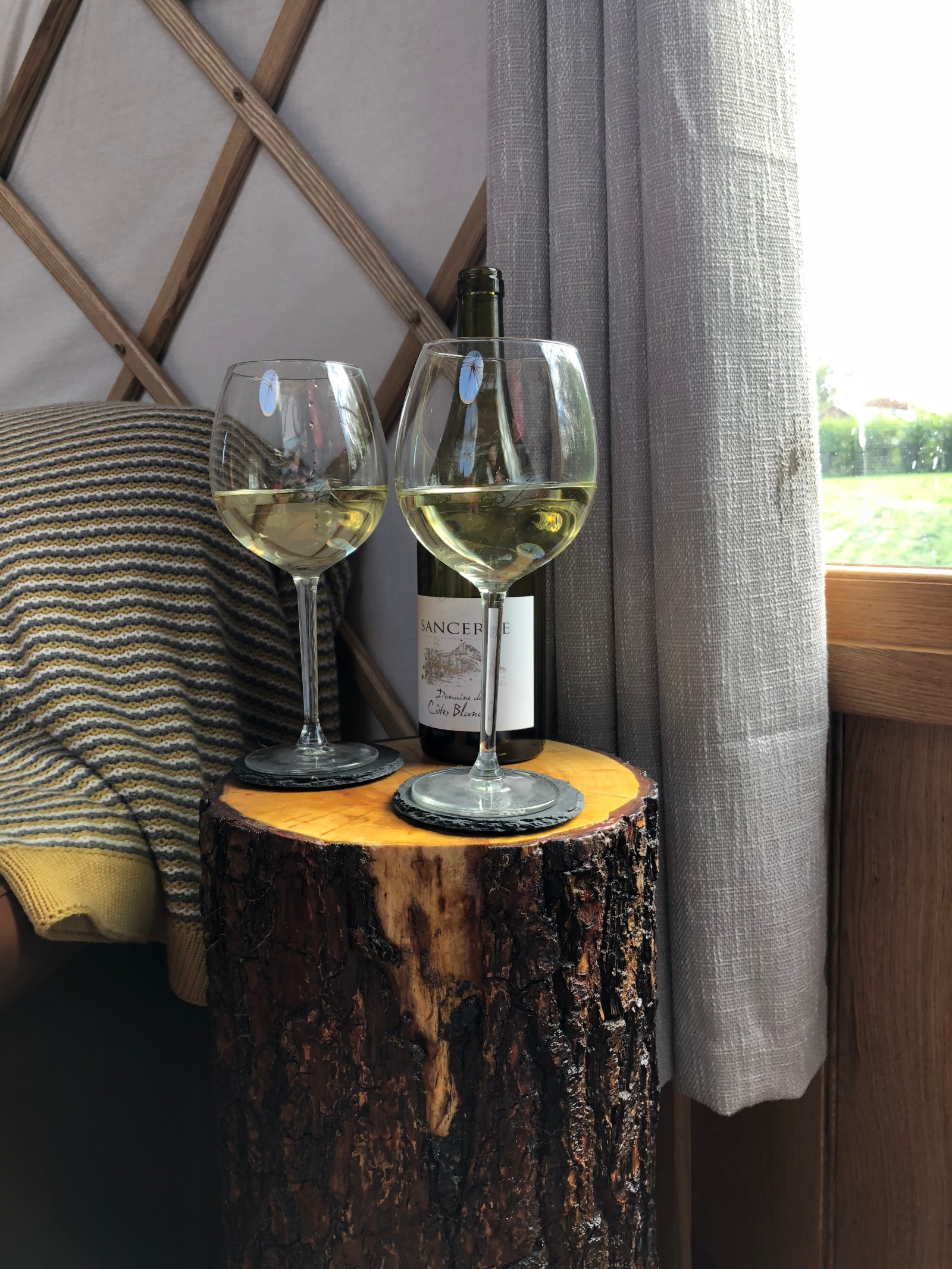 Bottle of Sancerre with two glasses on a tree trunk table